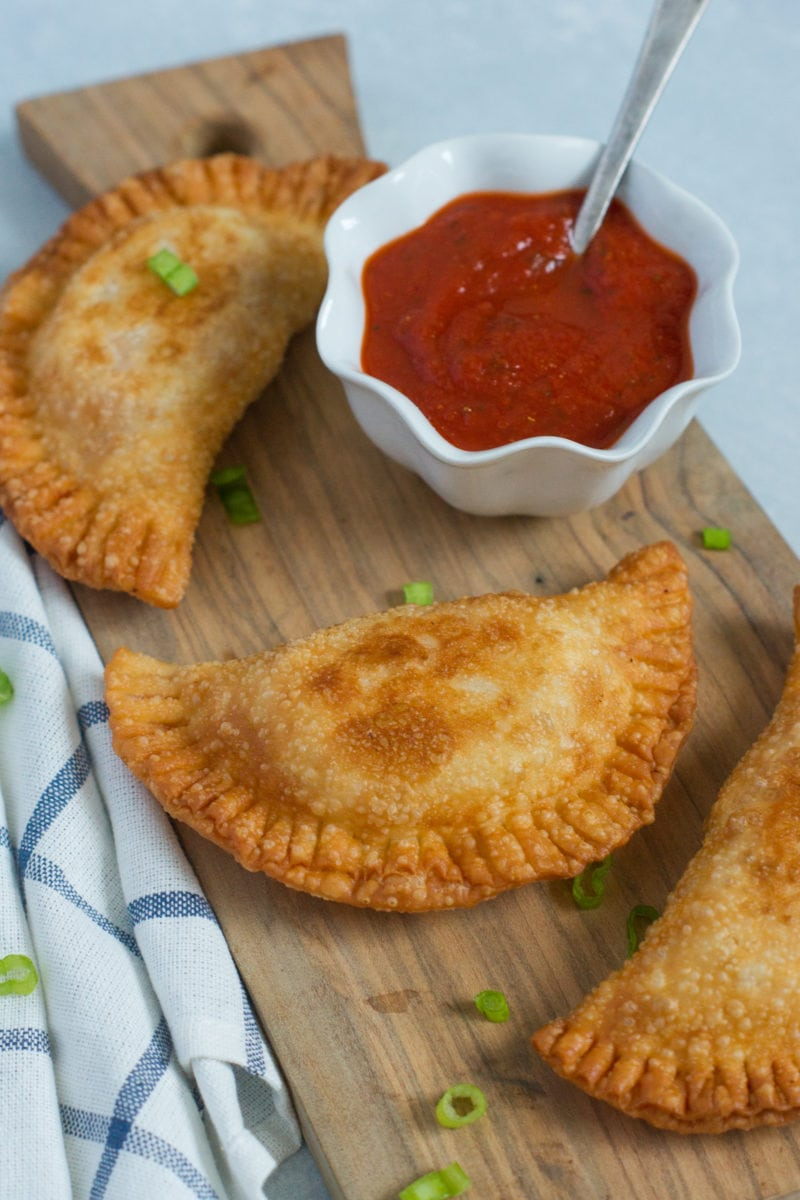 Close up of a chicken parm empanada next to a bowl of red dipping sauce.