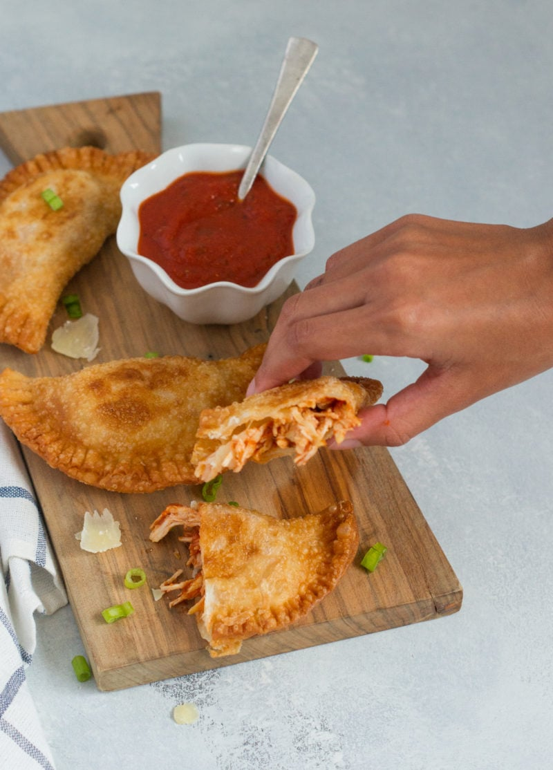 A hand picking up half of an empanada.
