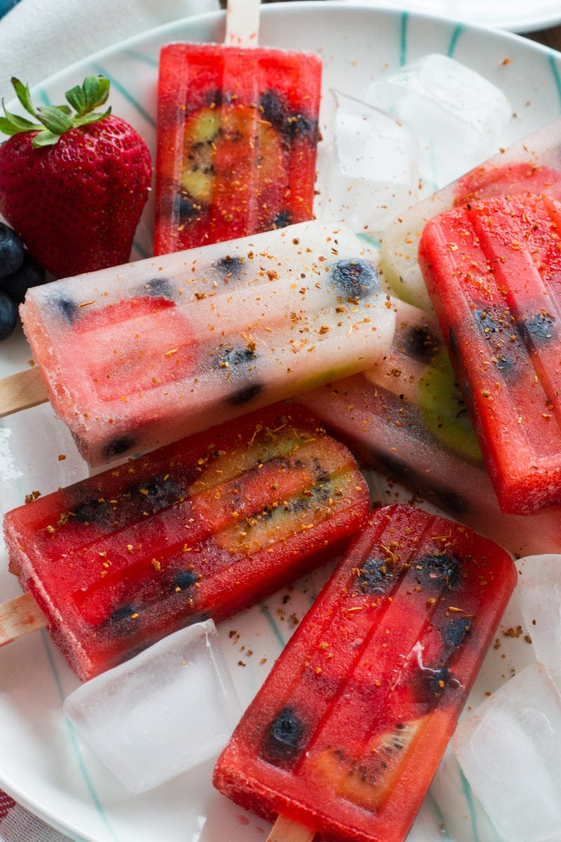 Real fruit popsicles on a plate with ice cubes