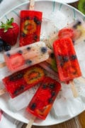 Overhead shot of different colored fruit popsicles sprinkled with spices.