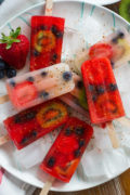 Easy Fruit Punch and Lemonade Popsicles with Tajin ~ Easy and refreshing fruit punch and lemonade popsicles filled with strawberries, blueberries and kiwi and sprinkled with Tajin for added flavor.