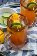 A sweet and spicy cocktail made with vegetable juice, mango tequila, Tajin, hot sauce and beer. This Spicy Mango Michelada is the perfect poolside drink this summer!#RedHotSummer #ad #IPSTOE