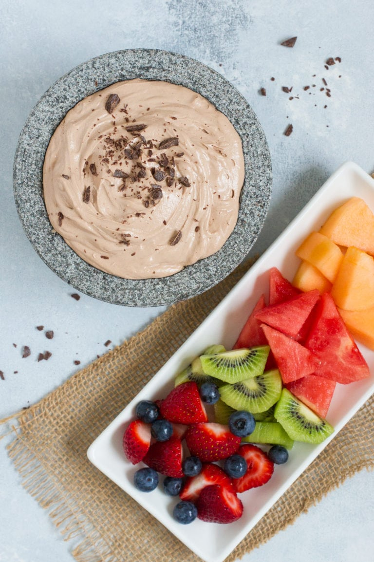 A tray of fruit next to a chocolate dip.
