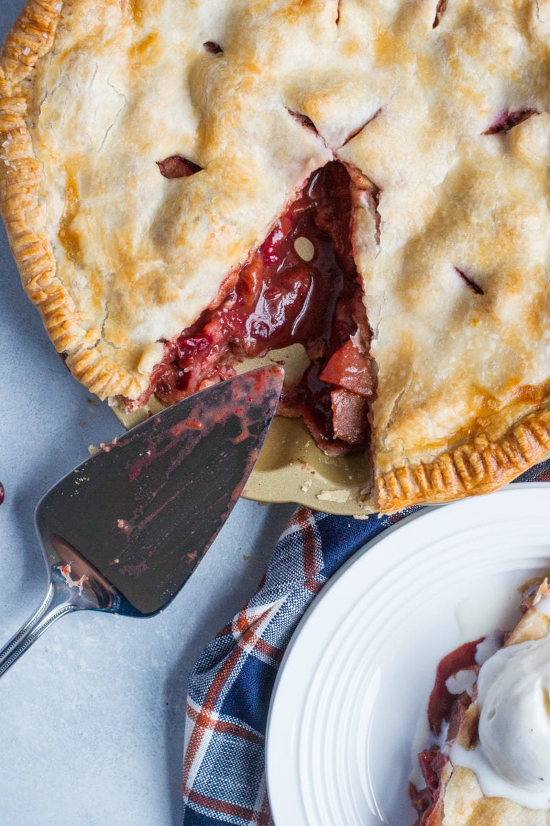 A pie slice next to the apple cranberry pie