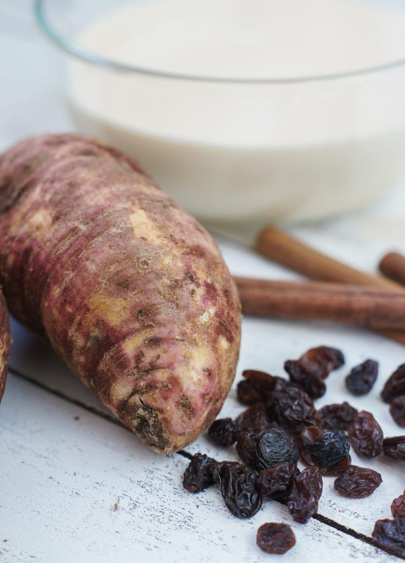 A sweet potato, raisins and cinnamon sticks.