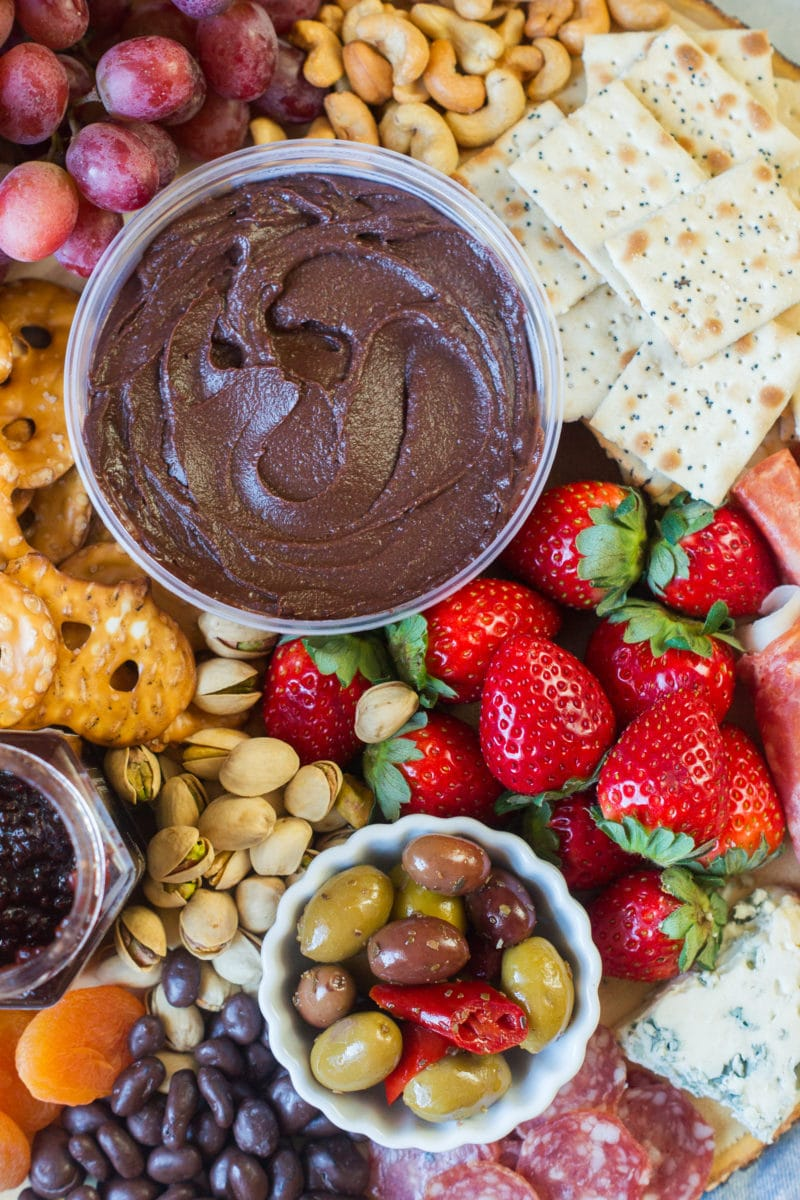 Strawberries next to a bowl of chocolate hummus, crackers and olives.