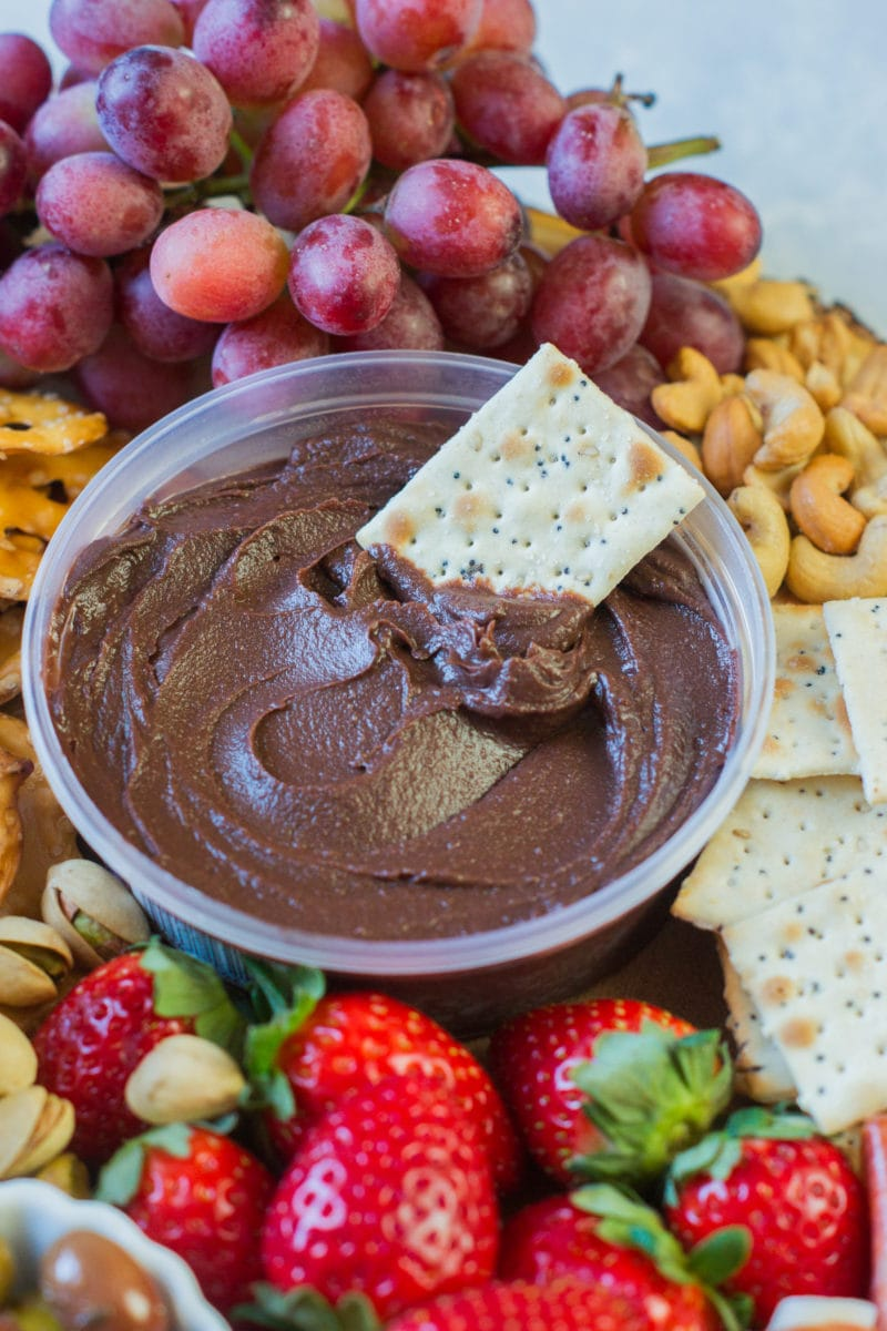 A cracker in a bowl of chocolate hummus.