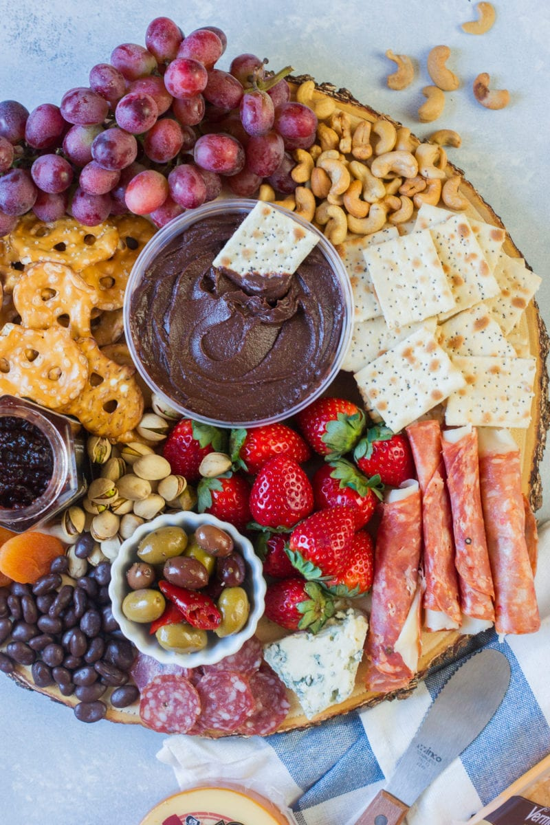 Cheese, ham, fruits, crackers and dips on a platter.