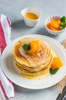 Mascarpone pancakes stacked on a white plate and topped with a mandarin glaze.