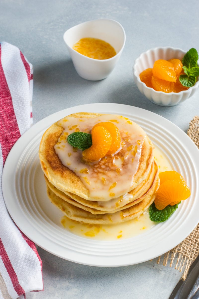 Mascarpone pancakes stacked on a white plate and topped with a glaze and mandarin slices.