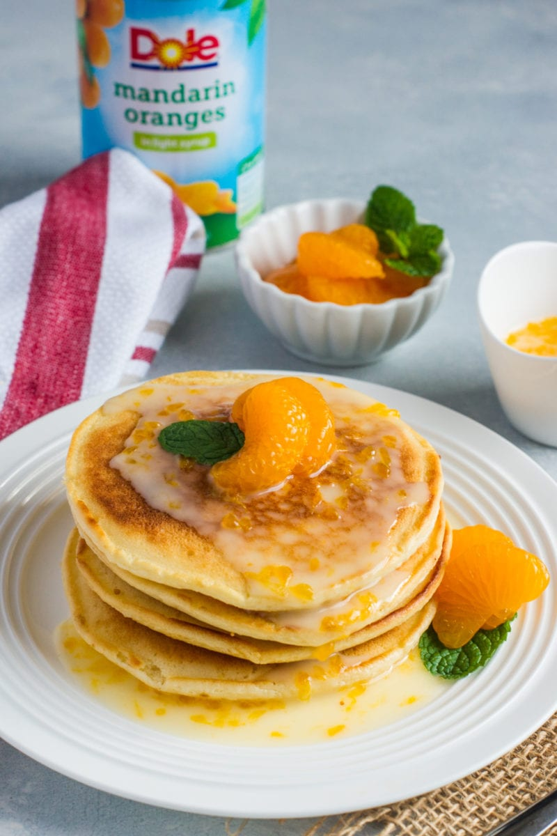 A stack of pancakes on a white plate with fruit and a glaze.