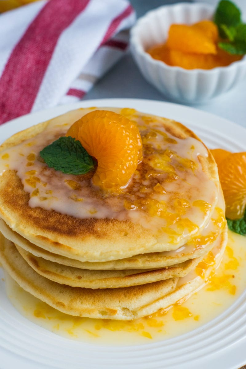 Close up of mandarin orange slices on top of a stack of pancakes.