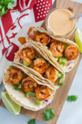 Three shrimp tacos next to a jar of sauce on a wooden chopping board.