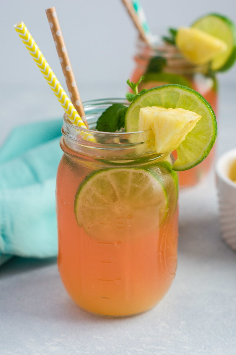 The mojito in a jar garnished with fresh pineapple, lime and mint.