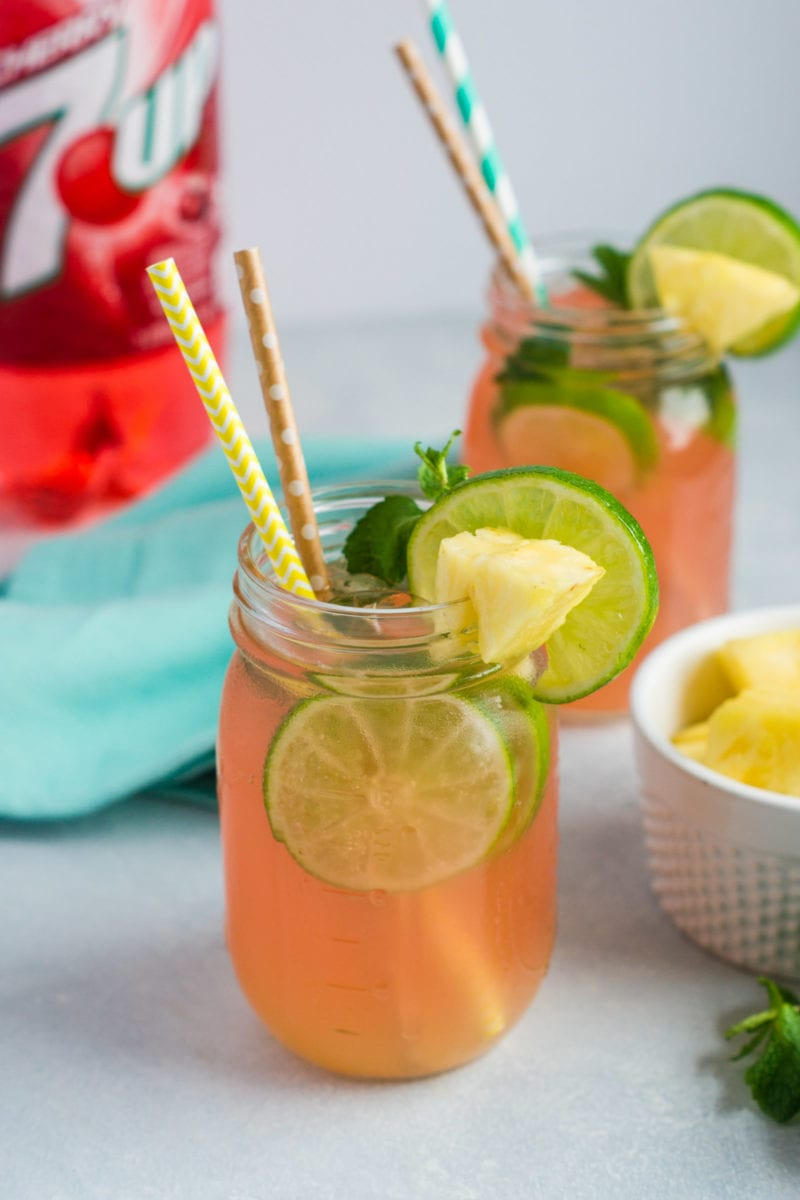 Two jars of cherry pineapple mojitos with straws and garnishes.