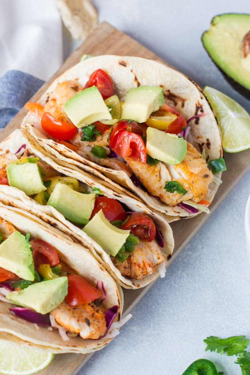 Delicious Fish Tacos made with a lime-dressed slaw, flounder fish and topped with avocado and a tomato, jalapeño and cilantro salsa all wrap in corn tortillas.