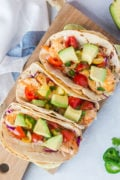 Delicious Fish Tacos made with a lime-dressed slaw, flounder fishand topped with avocado and a tomato, jalapeño and cilantro salsa all wrap in corn tortillas.