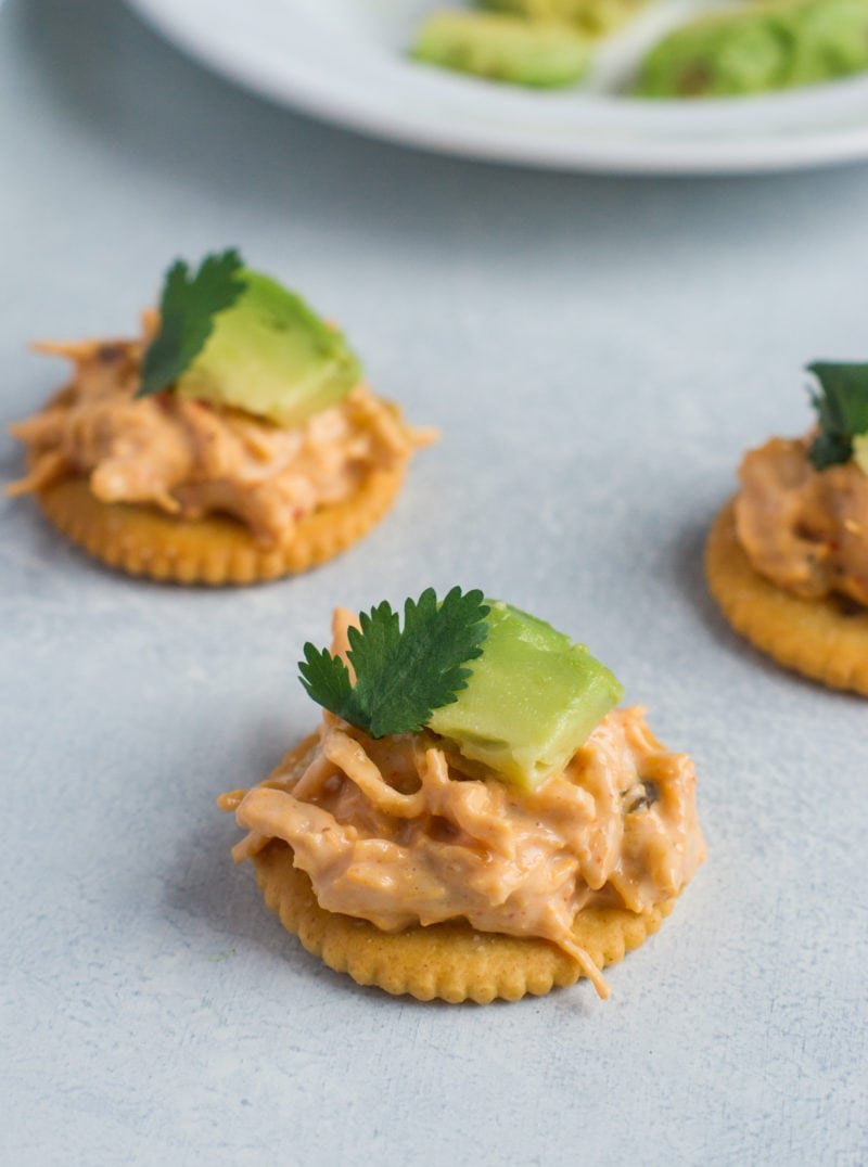 Ritz crackers topped with chicken nacho mix and avocado.