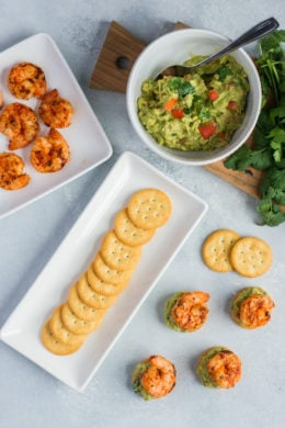 Crackers on a serving plate next to a bowl of guacamole and a plate of shrimp.