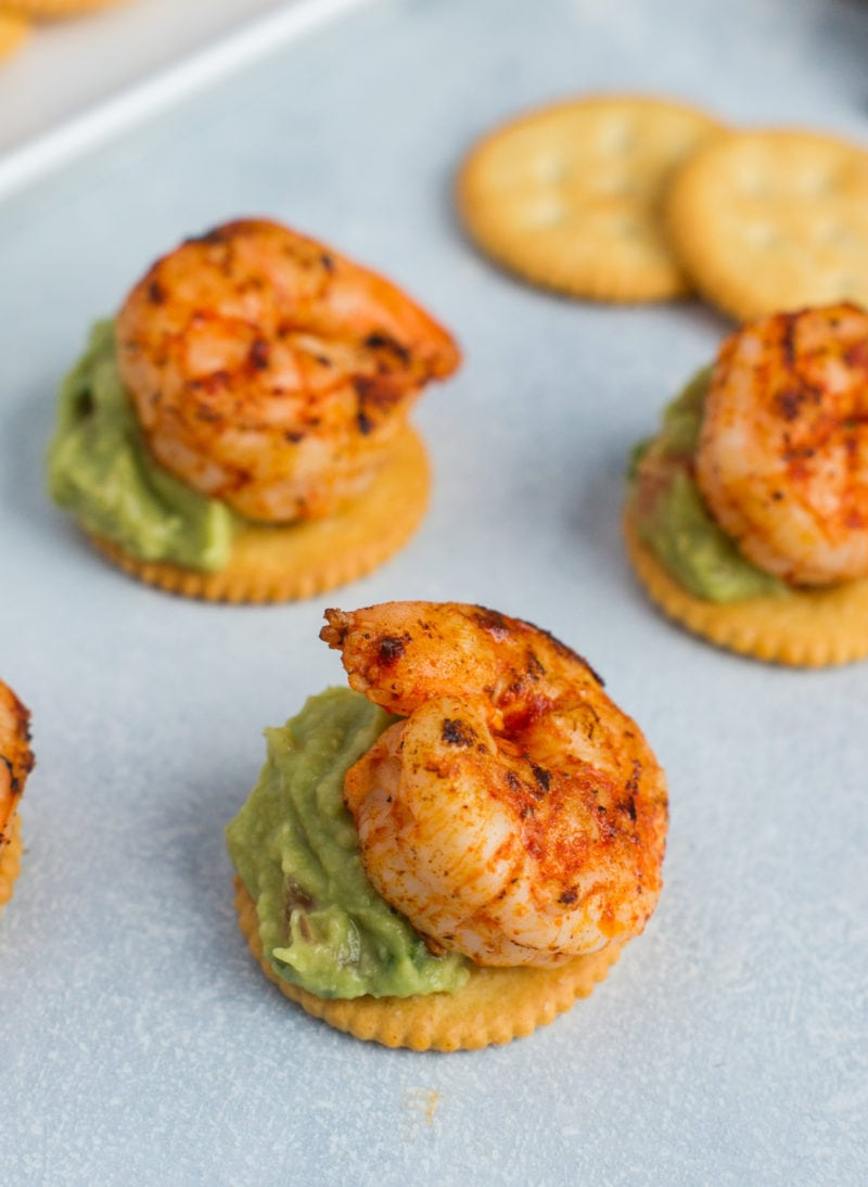 Three Ritz crackers topped with guacamole and a seared shrimp.