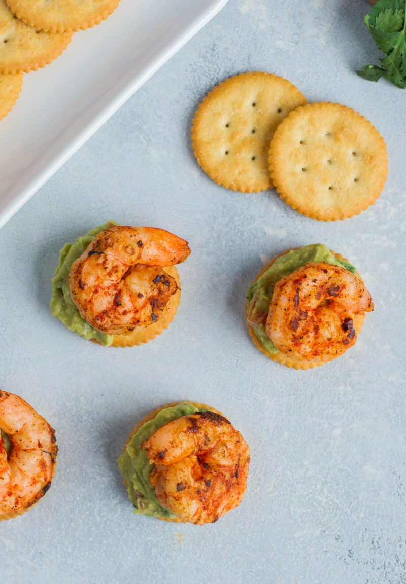 Overhead shot of four spicy shrimp and guacamole bites.