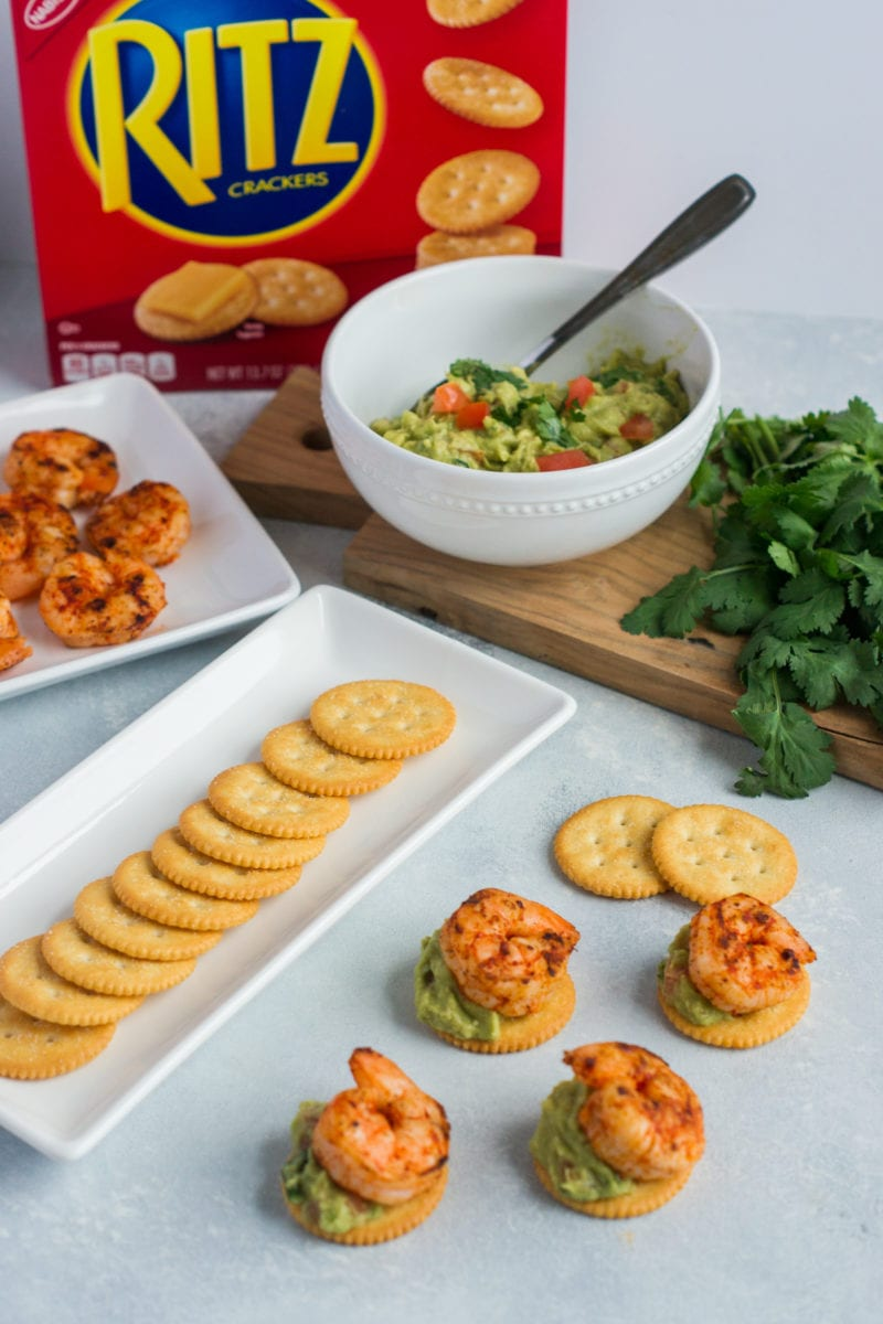 Crackers, shrimp and guacamole on plates next to the made up appetizers.