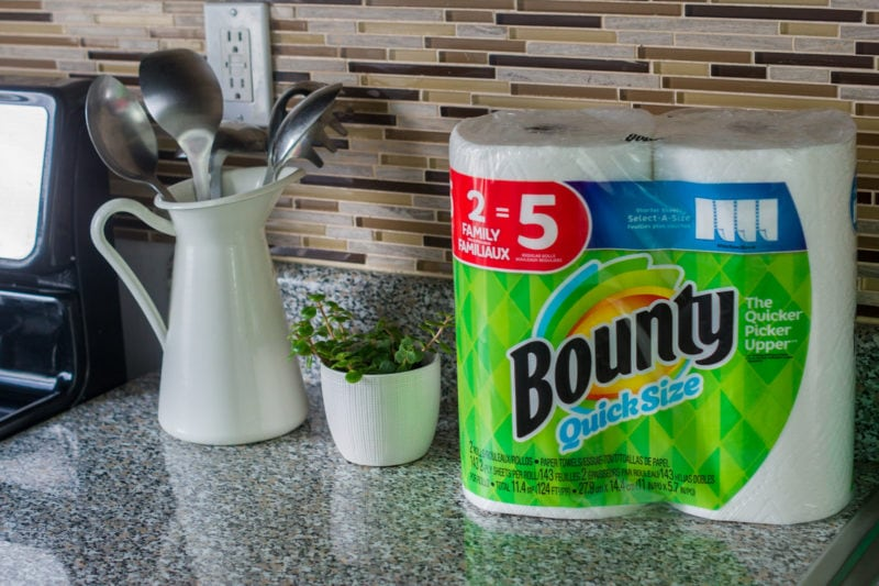 A kitchen counter with a pack of Bounty kitchen towel next to kitchen utensils.