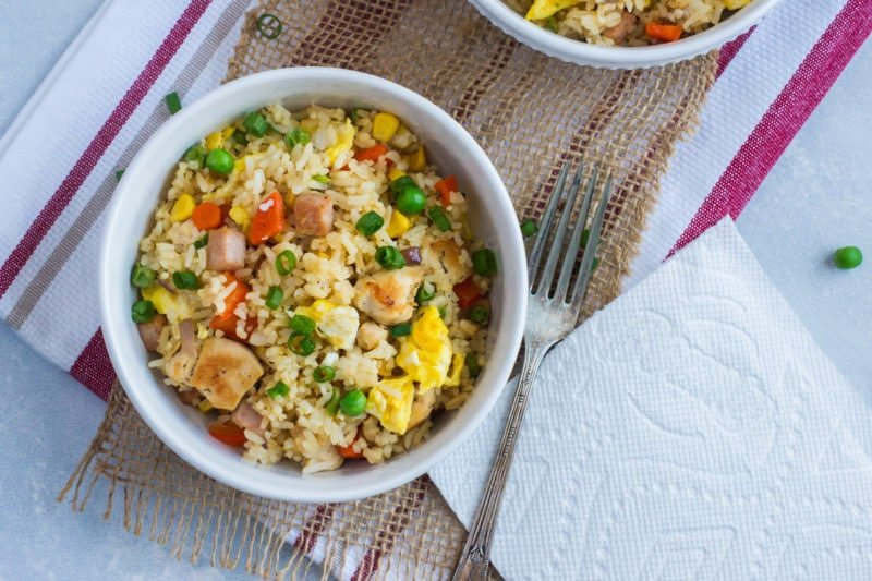 Rice with vegetables and chicken served in a white bowl.