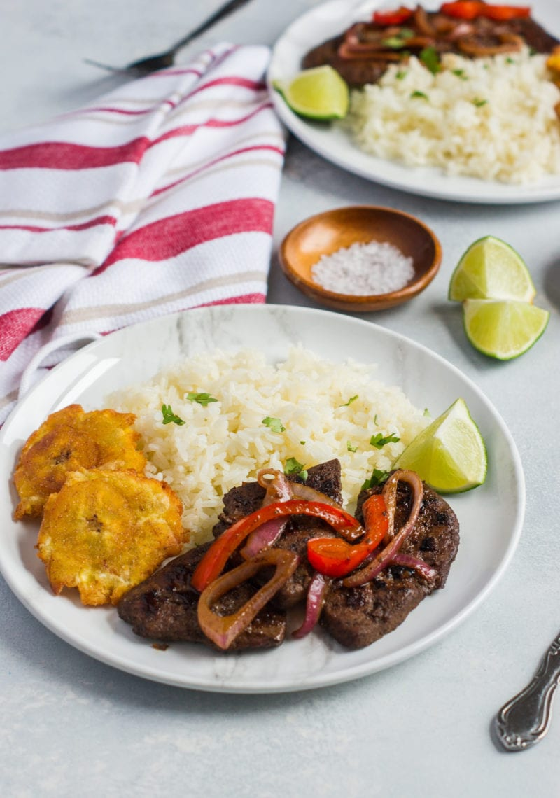 Liver an onions served on a plate with rice and tostones.