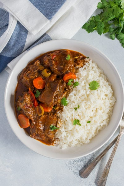 Traditional Dominican StyleSpicy Oxtail Stew (Rabo Encendio) made with beef oxtail, onions, peppers, garlic, cilantro, carrots, tomato sauce, latin seasonings.