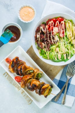 BBQ chicken skewers next to a bowl of BLT salad.