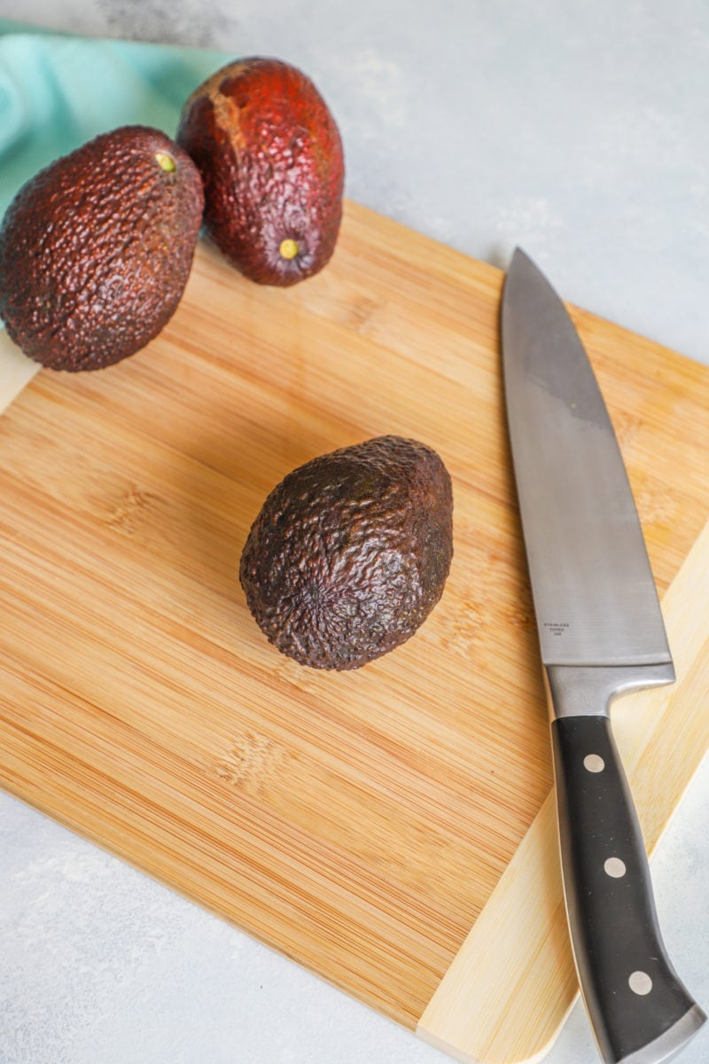 An avocado on a chopping board with a knife