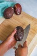 running the knife around the avocado lengthwise