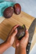 giving avocado a twist to separate in two halves