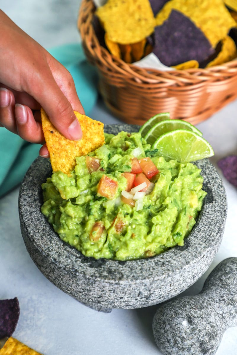 A hand holding a tortilla chip, dipping into the guacamole.