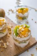 Tropical yogurt parfaits served in three glass jars.
