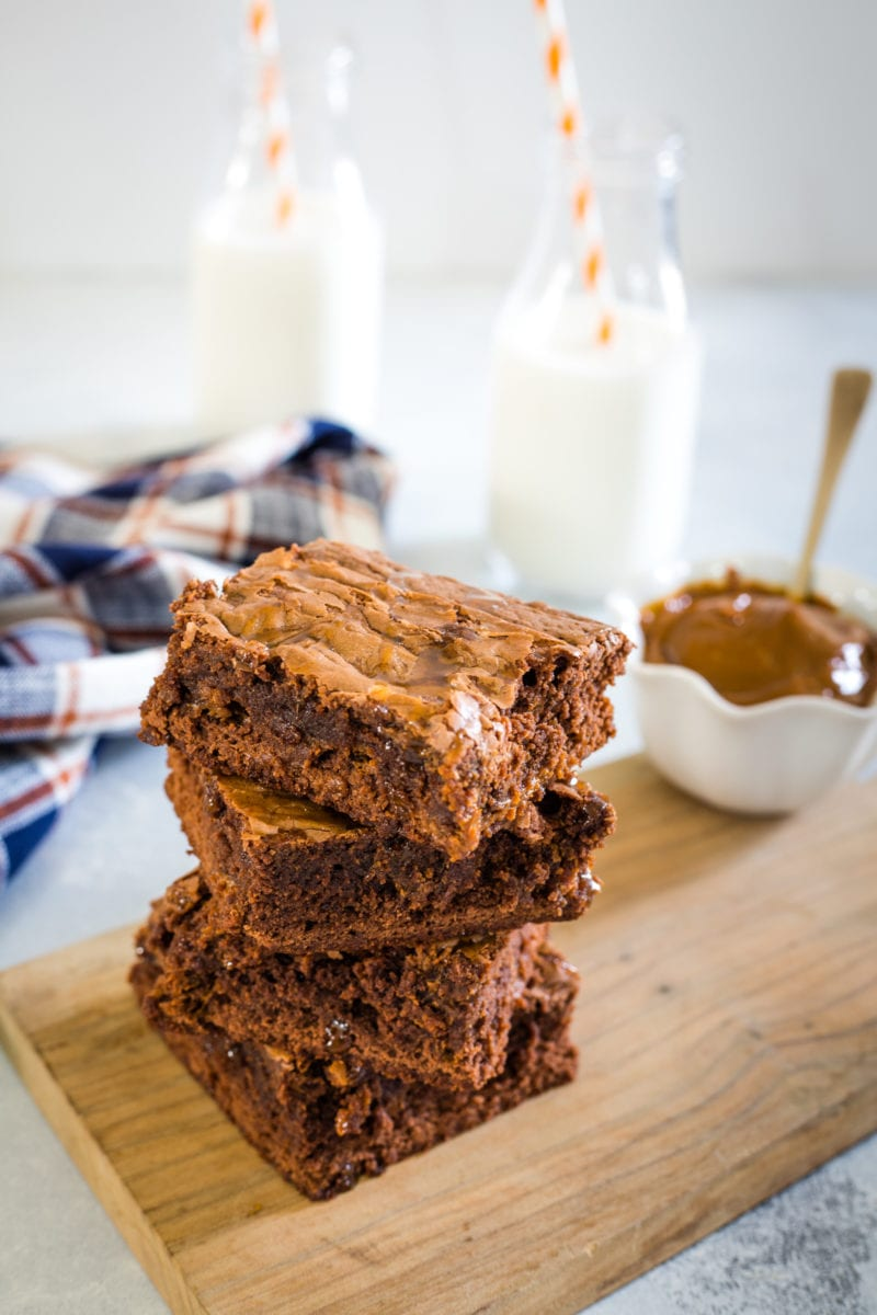 Three dulce de leche brownies stacked on top of each other.