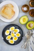 Hard boiled eggs on a black plate next to toast and avocado