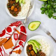 Slow cooker lentil stew served in two bowls with rice and sliced avocado.