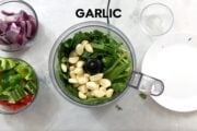 adding herbs and garlic to food processor