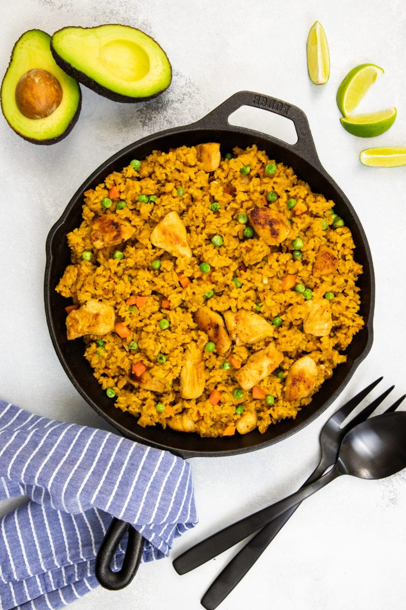 Chicken and Rice Mexican Style on a cast iron skillet with a side of avocado