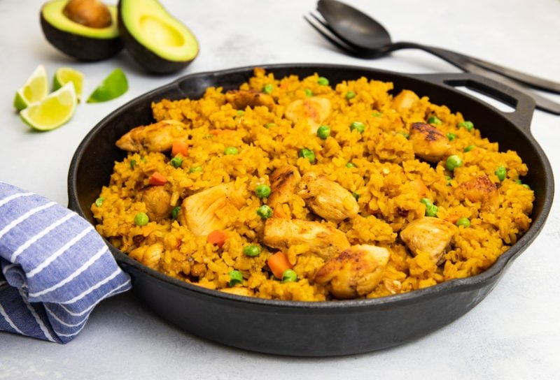 A cast iron skillet with chicken, rice and peas.