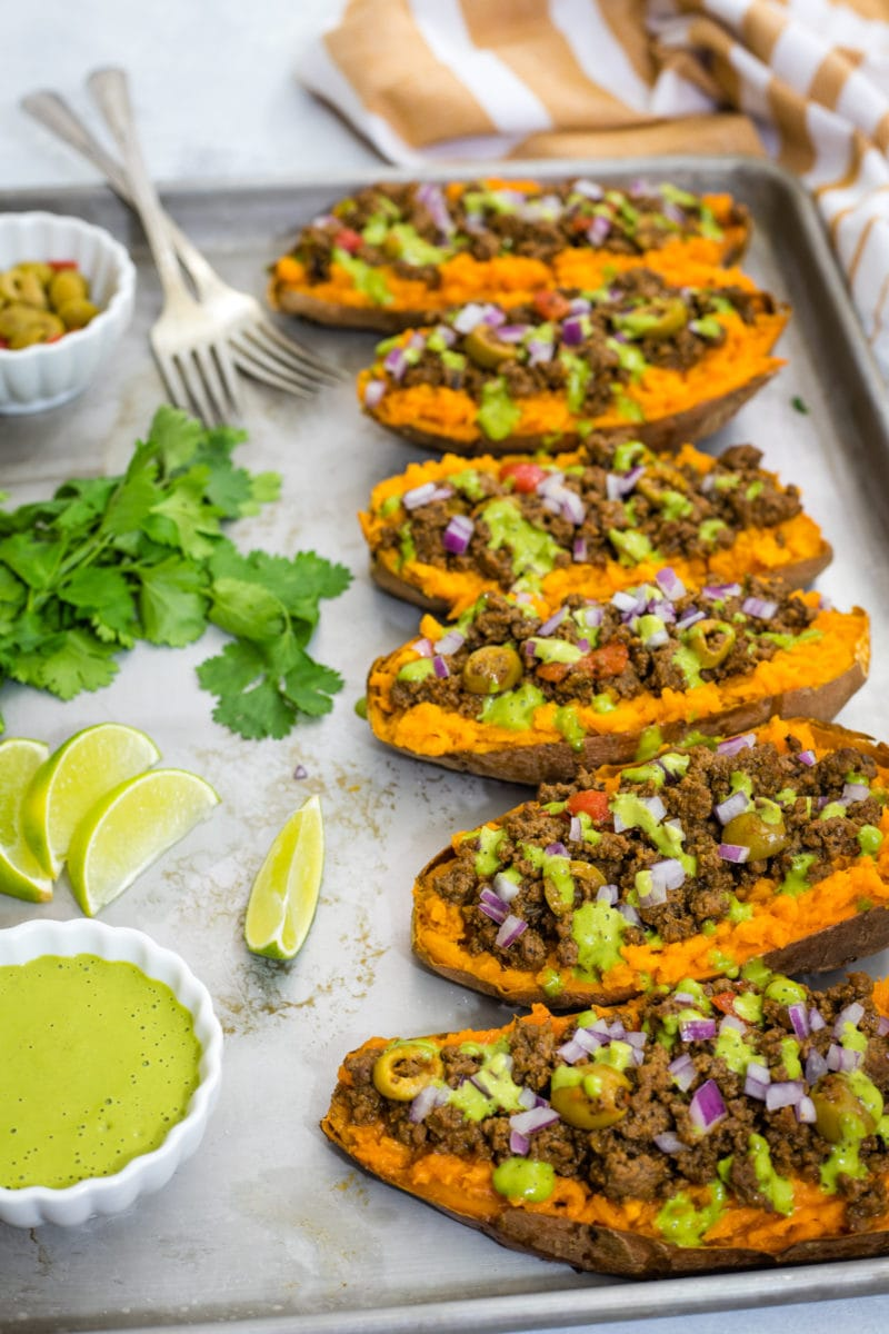 Stuffed sweet potatoes next to lime wedges