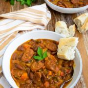 Chorizo and bean stew served in a bowl with crusty bread.