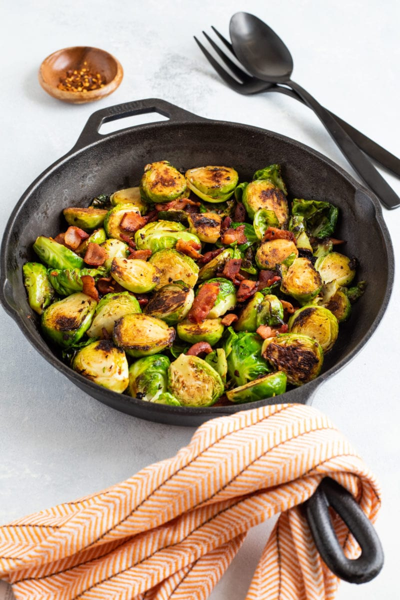 A cast iron skillet with crispy Brussels sprouts and bacon.