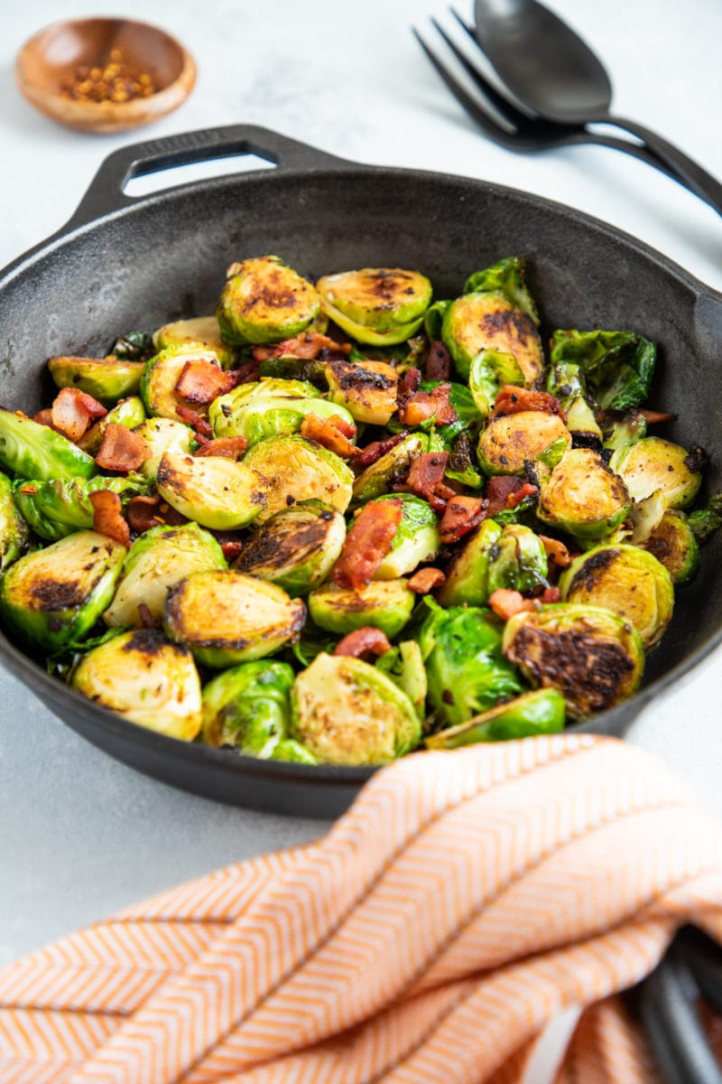 Cooked Brussels sprouts with bacon pieces in a skillet.