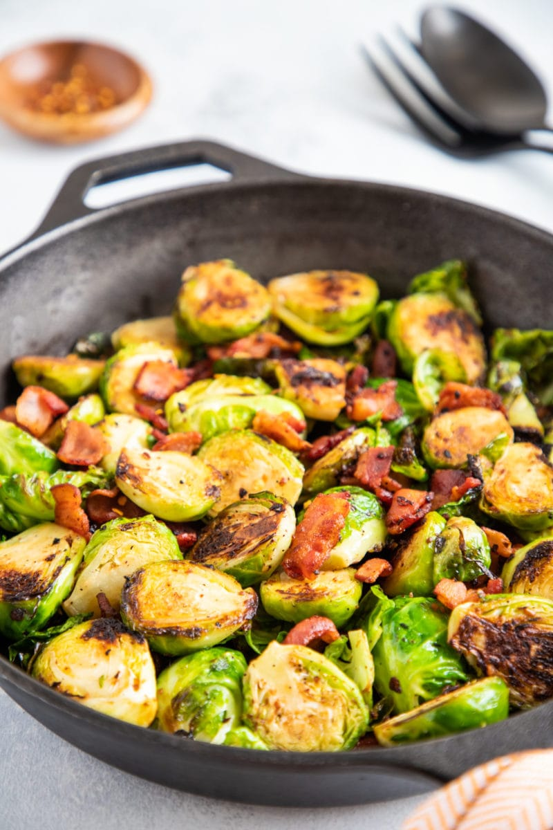Close up of bacon and Brussels sprouts in a skillet.