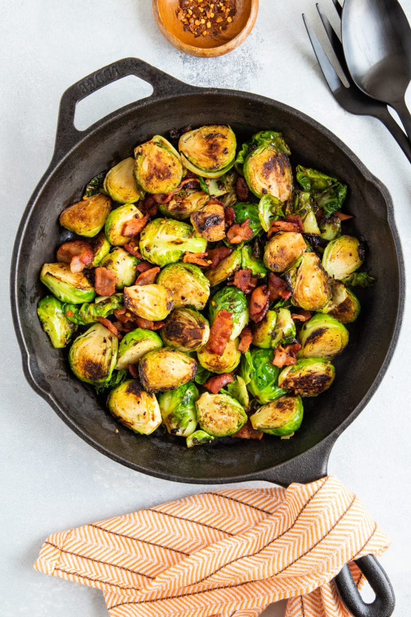 Sautéed Brussels sprouts and bacon in a cast iron skillet.