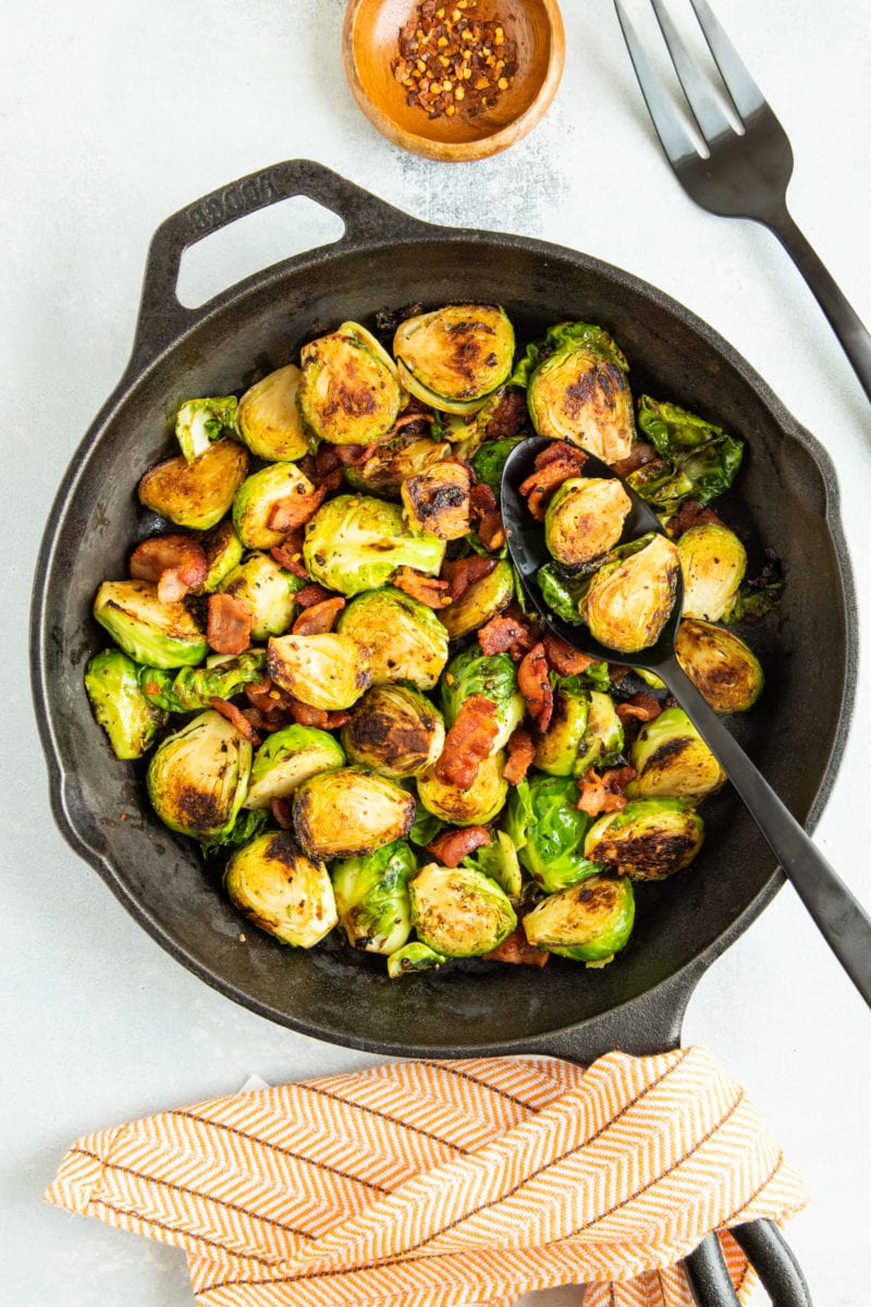 A spoon serving the sprouts and bacon from a skillet.