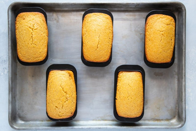 The loaves of cornbread in tins after being baked.